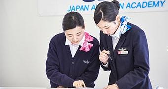 空港受付の練習をする学生