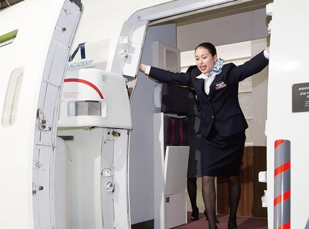 航空機のドアを開ける実習をする学生